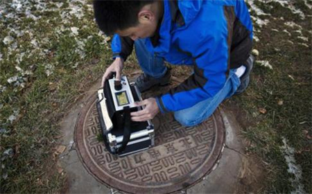 Beijing resident Tan Liang takes readings of microscopic air pollutants on a PM2.5 detector