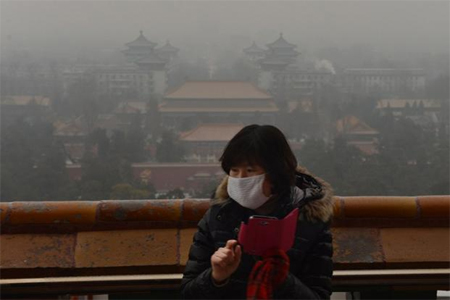 A Chinese tourist takes photos from the historic Jingshan Park as smog continues to shroud Beijing