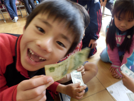 A 2nd grade boy with a Chinese 1 Yuan note