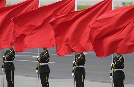 Members of the People's Liberation Army guard of honour stand with red flags during an official welcome ceremony outside the Great Hall of the People, in Beijing