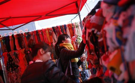 Customers select hats at a street stall in the business area of Jiaozuo, China's central Henan province. Credit: REUTERS/Aly Song