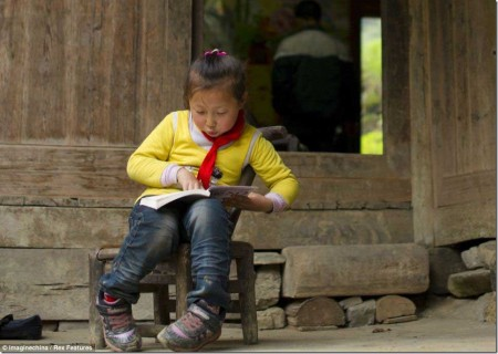 At home: 5-year-old Yu Xinxin, who climbs the ladders to school every day, reading before she sets off on her long morning journey
