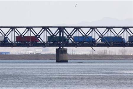 Trucks drive on the Friendship Bridge over the Yalu River which connects North Korea's Sinuiju to China's Dandong