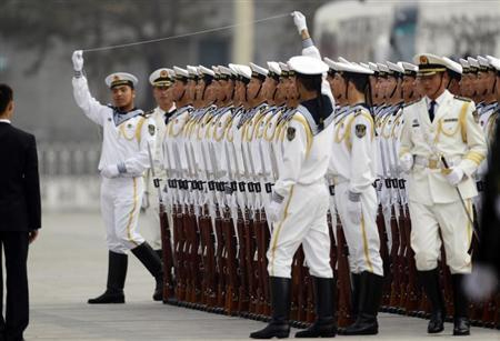 Members of the People's Liberation Army's navy guard of honour prepare to use a string to ensure that soldiers stand in a straight line before an official welcome ceremony outside the Great Hall of the People