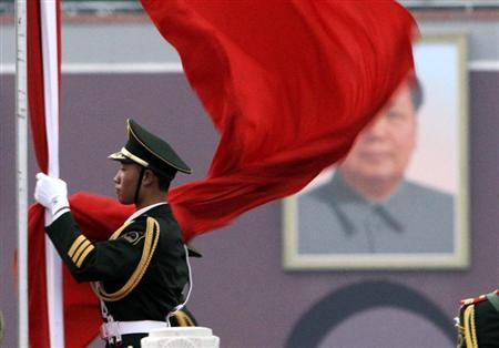 A paramilitary policeman prepares for a national flag-lowering ceremony in front of a portrait of the late chairman Mao Zedong on Tiananmen Square in Beijing