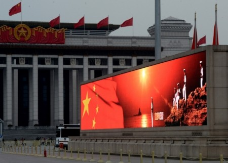 An image of the Chinese flag and sailors standing on Spratly Islands is displayed on a big screen in Tiananmen Square, March 2, 2013.
