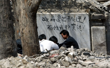 "Chinese words reading ""Government get out of the eviction business, commoners protect the constitution"" are painted on a house marked for forced eviction in Beijing. Photo: AP"