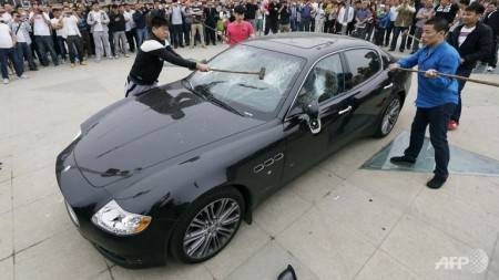four-sledgehammer-wielding-men-destroy-a-maserati-outside-the-qingdao-convention-center-in-china-on-may-14-2013-4