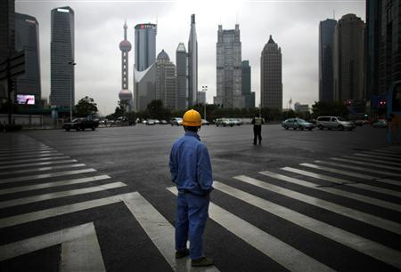 A construction worker looks at Pudong financial district as he waits to cross an avenue in Shanghai