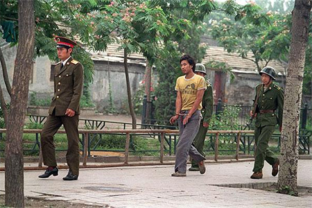 A handcuffed man is led by Chinese soldiers on a street in Beijing on 14 June 1989 as the authorities looked to prosecute and punish anyone connected with the demonstrations.