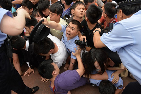 Two officers are crushed when police lose control of the crowd during David Beckham's visit to a Shanghai university