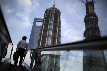 A man rides an escalator near Shanghai Tower (R, under construction), Jin Mao Tower (C) and the Shanghai World Financial Center (L) at the Pudong financial district in Shanghai. Credit: Reuters/Carlos Barria