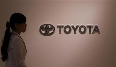 A woman walks past Toyota Motor's logo at the company showroom