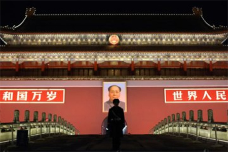 A paramilitary police officer stands guard in front of a portrait of former Chinese leader Mao Zedong at Tiananmen Gate in Beijing