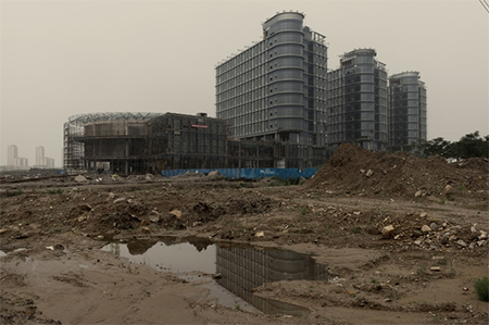 The steel mill at the heart of Caofeidian, which is outside the city of Tangshan about 140 miles southeast of Beijing, is losing money. Nearby, this commercial and office building is still under construction with little activity