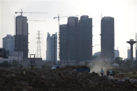Workers walk at a demolished quarter at an abandoned steel plant in Wuxi, Jiangsu province