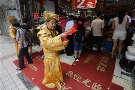 A salesperson, dressed as the Chinese god of fortune, hands out leaflets for a jewellery shop at a shopping district in Beijing