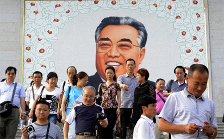 Chinese tourists leave after paying homage to a giant portrait of Kim Il-sung at a square in Rason, but the mausoleum for Kim and his son Kim Jong-il is not on their itinerary