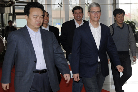 Apple Chief Executive Tim Cook walked with employees as he arrived at the headquarters of China Telecom