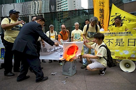 Protesters set fire to a Japanese flag after placing flower wreaths dedicated to those killed in World War II outside the Japanese consulate in Hong Kong. (Tyrone Siu/Reuters)