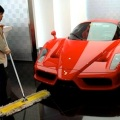 A 2011 file photo of a cleaner sweeping the floor next to a Ferrari in a Beijing luxury car showroom