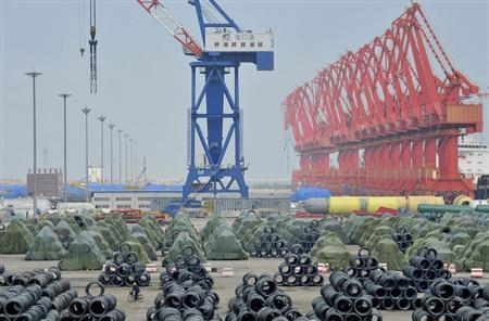 A worker rides his bicycle past piles of steel coils for export at a port in Yingkou, Liaoning province