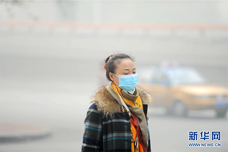A Harbin citizen walks in thick smog that has reduced visibility below 50 meters on October 21