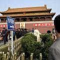 A tourist takes photos near the partially damaged stone bridge in front of Tiananmen Gate, in Beijing. File photo