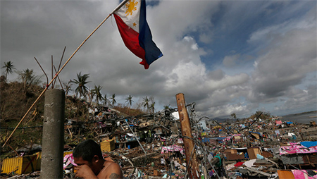 The Philippine flag flies over typhoon ravaged Tacloban city as survivors wait for aid