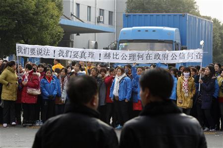 Two men watch as workers on strike block the entrance gate of Hi-P International factory in Shanghai.