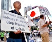 Japanese nationalists carry national flags and placards during a rally over the Senkaku islands issue, known as the Diaoyu islands in China, in Tokyo on September 18, 2012. Two Japanese activists landed on an island at the centre of a bitter dispute with China on September 18, the government in Tokyo said, as fresh anti-Japanese protests rocked Chinese cities. AFP PHOTO / Yoshikazu TSUNO