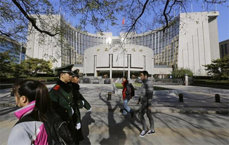 People walk past the headquarters of the People's Bank of China (PBOC), the central bank, as two paramilitary police officials patrol around it in Beijing November 20, 2013