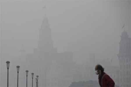 A man wears a face mask while walking on the Bund during a hazy day in downtown Shanghai December 6, 2013