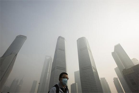 A man wears a mask while walking on a bridge during a hazy day in Shanghai's financial district of Pudong December 5, 2013