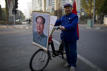 Qiu, a 65-year-old retired shipyard worker wearing a Red Army hat, poses for a photograph with his bicycle bearing a portrait of China's late Chairman Mao Zedong on a street in Shanghai