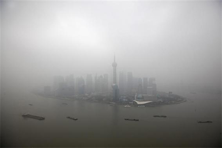 The financial district of Pudong is seen on a hazy day in Shanghai, in this file picture taken January 21, 2013. China's government is struggling to meet pollution reduction targets and has pledged to spend over 3 trillion yuan ($494 billion) to tackle the problem, creating a growing market for companies that can help boost energy efficiency and lower emissions.