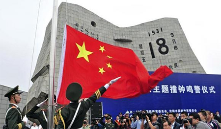 Paramilitary policemen hoist a Chinese national flag during a memorial ceremony on the 82nd anniversary of Japan's invasion of China at the September 18 Museum in Shenyang, Liaoning province, September 18, 2013
