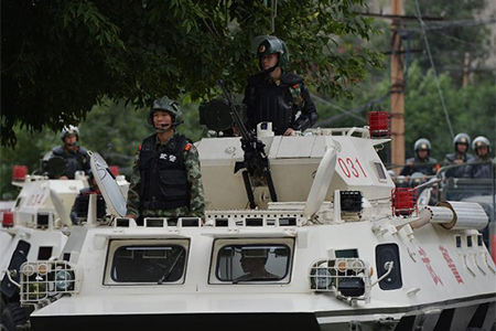 Chinese paramilitary police ride in armoured vehicles during a 'show of force' ceremony in Urumqi after a series of terrorist attacks recently hit Xinjiang Province