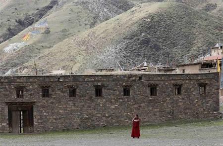 A Tibetan monk uses a mobile phone near the Dzamthang Jonang monastery in Barma township