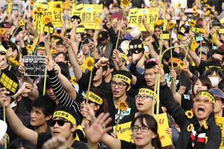 Demonstrators holding sunflowers shout slogans in front of the Presidential Office in Taipei March 30, 2014 Credit: Reuters/Toby Chang