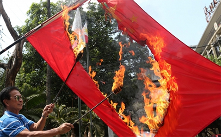 Filipino retired police officer Abner Afuang burns a Chinese flag, in protest over territorial disputes at a shoal in the South China Sea