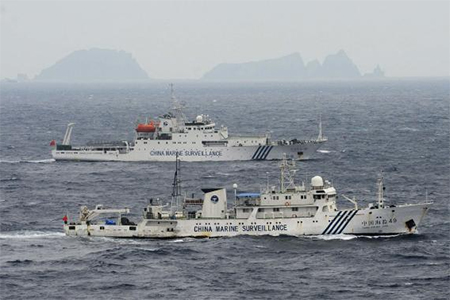 An aerial photo shows Chinese marine surveillance ships Haijian No. 49 (front) and Haijian No.50 cruising in the East China Sea, as the islands known as the Senkaku isles in Japan and the Diaoyu islands in China are seen in the background