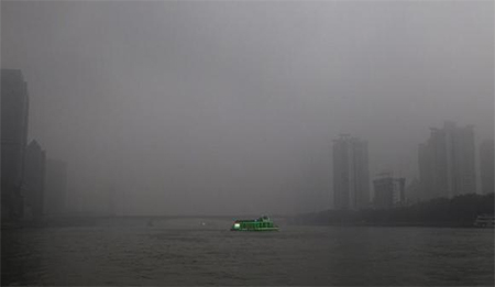 A tourist boat, decorated with green lights, travels on the Pearl River amid heavy haze in Guangzhou, Guangdong province