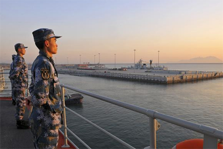 Chinese naval soldiers stand guard on China's first aircraft carrier Liaoning, as it travels towards a military base in Sanya, Hainan province