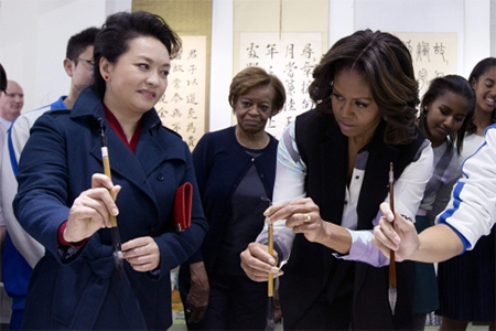 Peng Liyuan shows Michelle Obama how to hold a writing brush as they visit a Chinese traditional calligraphy class at the Beijing Normal School