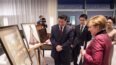 German Chancellor Angela Merkel presents Chinese President Xi Jinping with a map of China from the 18th century in Berlin, Germany