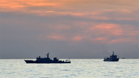 two Chinese surveillance ships which sailed between a Philippines warship and eight Chinese fishing boats to prevent the arrest of any fishermen in the Scarborough Shoal, a small group of rocky formations whose sovereignty is contested by the Philippines and China, in the South China Sea, about 124 nautical miles off the main island of Luzon April 10, 2012