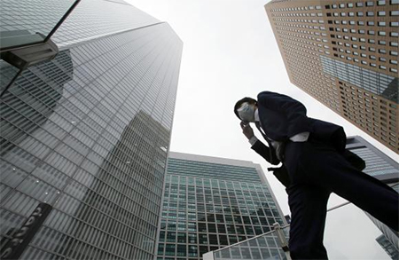 A businessman walks in Tokyo's business district