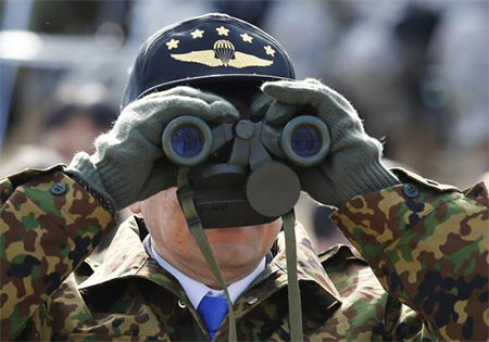 Japan's Defence Minister Itsunori Onodera uses a pair of binoculars as he inspects an annual new year military exercise by the Japanese Ground Self-Defense Force 1st Airborne Brigade at Narashino exercise field in Funabashi, east of Tokyo January 12, 2014