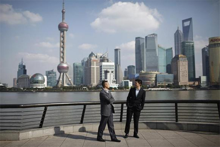Businessmen walk on the Bund near the Huangpu River in front of the financial district of Pudong in Shanghai November 21, 2011